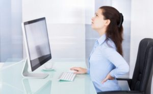 woman sitting at the computer having back pain