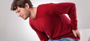 a man in red t-shirt suffering from aching back