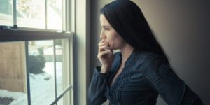 depressed woman looking at the window