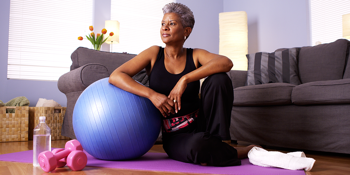 woman exercises at home with yoga ball