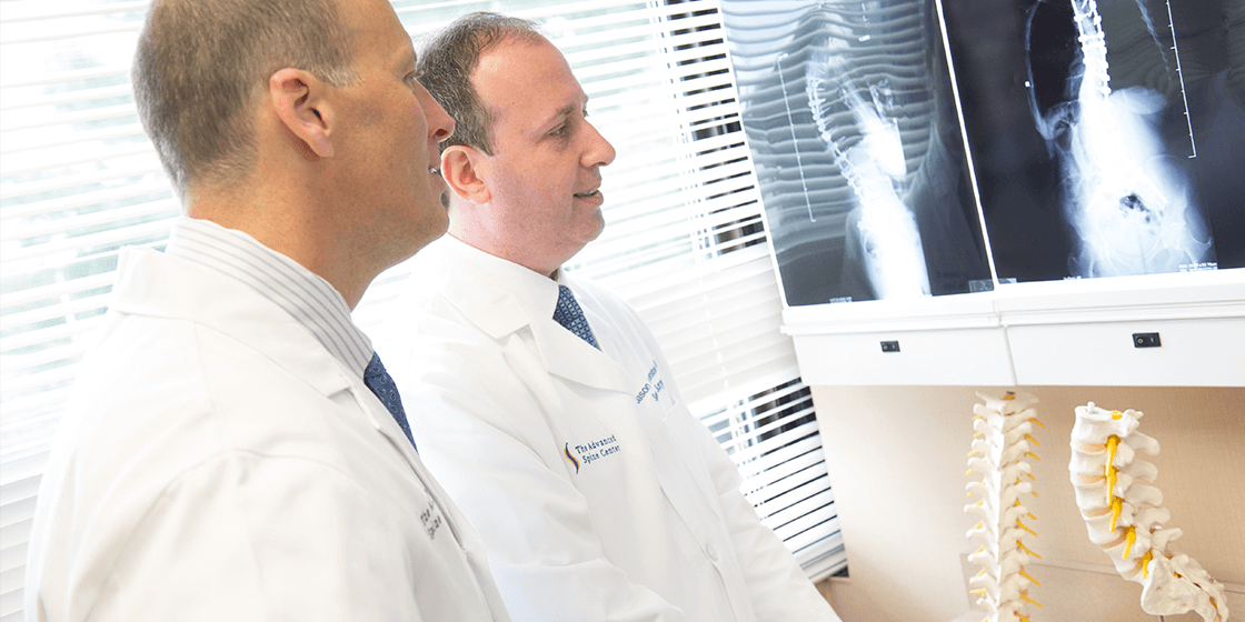 dr. jason lowenstein & dr. george naseef examining spine x-ray