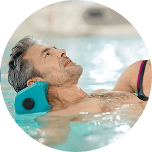 man floats in pool during aquatic therapy