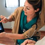 nurse showing woman x-ray of lumbar spinal stenosis