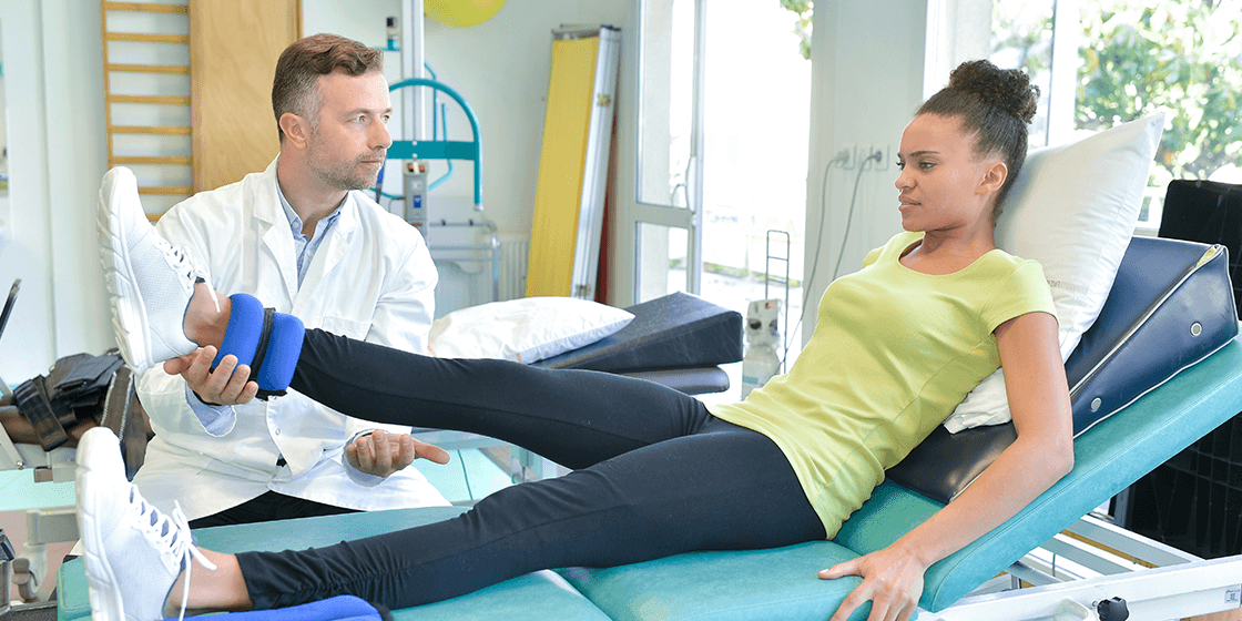 woman with sciatica completes hip flexor exercise with physical therapist