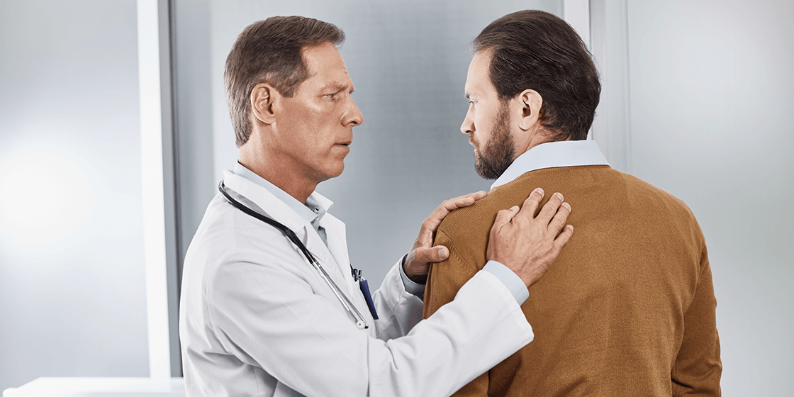 doctor examining patient with upper back pain