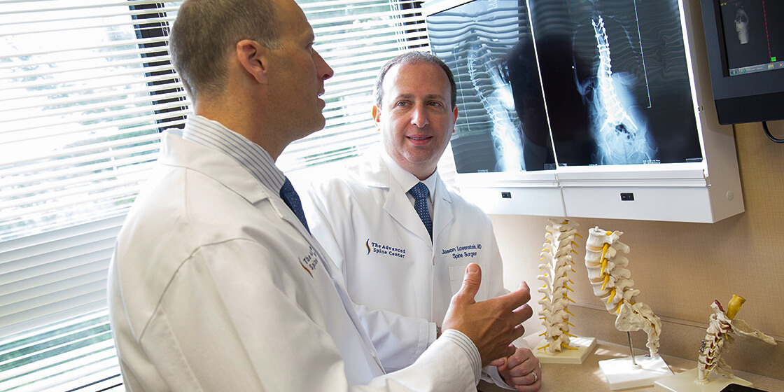 dr. lowenstein examines scoliosis x-ray